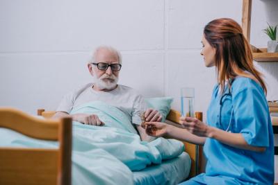 caregiver giving medicine to senior man