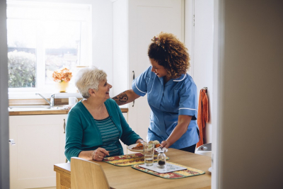 caregiver giving meal to senior woman