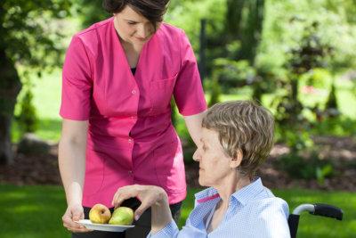 caregiver giving fruits senior woman