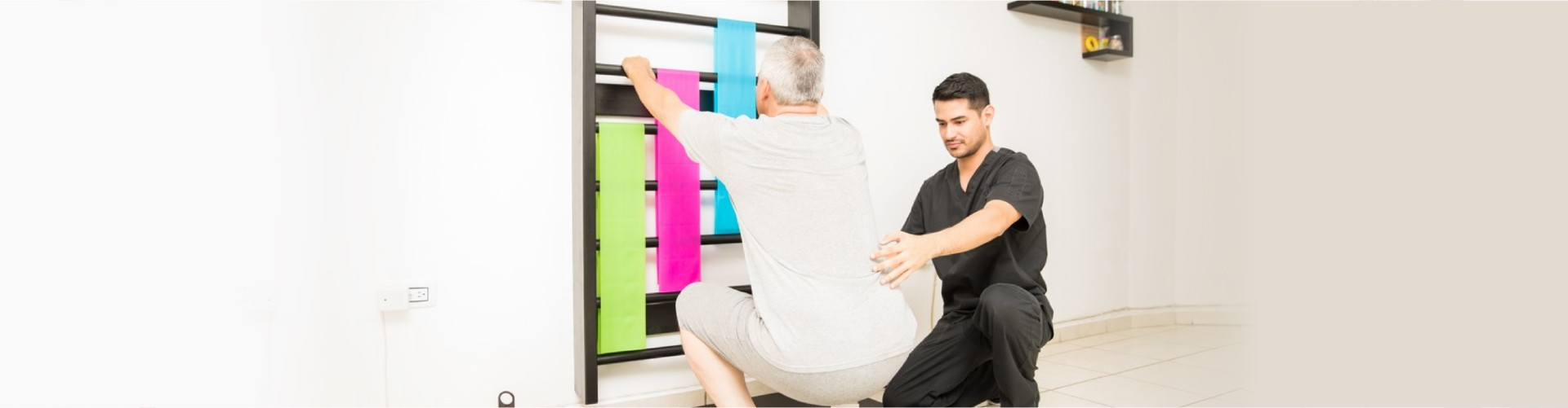 Young physical therapist assisting mature men doing squats in clinic