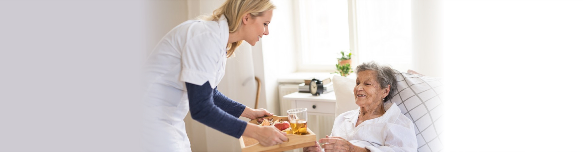 Ayoung health visitor bringing breakfast to a sick senior women lying in bed at home.