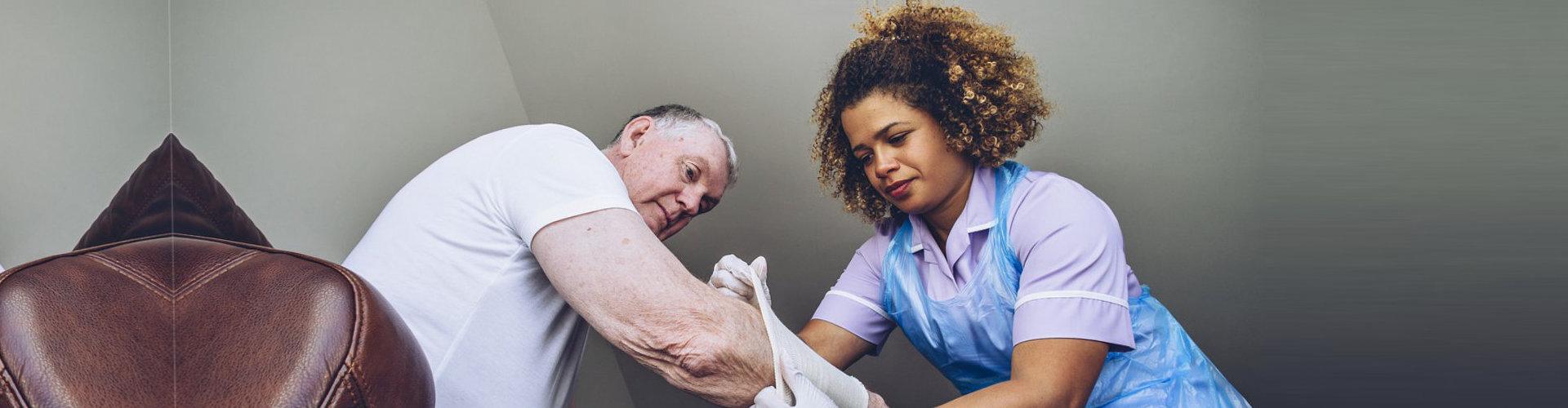 caregiver putting bandage on senior man's arm